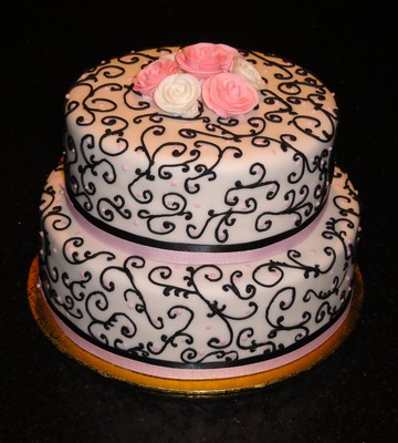2 Tiered cake with scrollwork piping and pink accents.